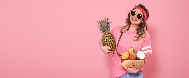 ピンクのtシャツとメガネの美しい少女は、ピンクの背景に果物の完全なストローバッグを保持しています。