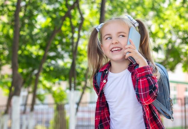 路上で電話で話しているバックパックと幸せな女子高生。白いtシャツと格子縞のシャツ