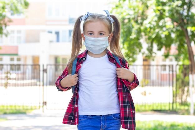 バックパック付き防護マスクで幸せな女子高生。白いtシャツと格子縞のシャツ