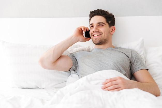 白いリネンのベッドで一人で横になっていると、スマートフォンで話している笑顔のカジュアルなtシャツでブルネットの魅力的な男性のイメージ