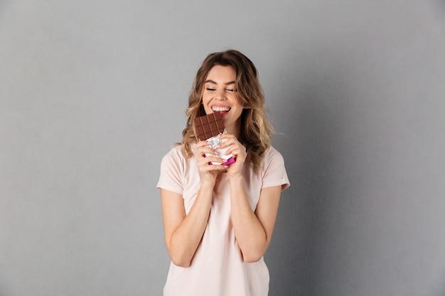 灰色の目を閉じてチョコレートを食べるtシャツで陽気な女性のイメージ