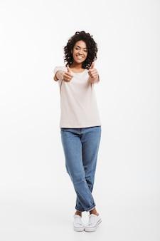 白い壁に分離されたジーンズとtシャツ笑顔とジェスチャー親指を身に着けている豪華なアメリカ人女性の完全な長さの肖像画