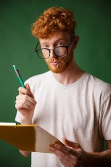 フォルダーとペンを保持している白いtシャツでスマートリードヘッドのひげを生やした男