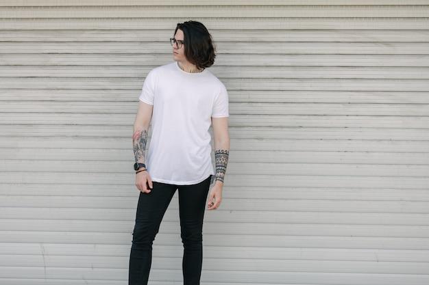 白い空白のtシャツを着ている流行に敏感なハンサムな男性モデル