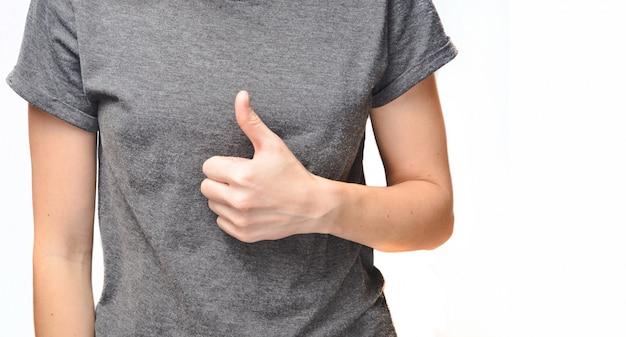 上向きに発生した女性の手の親指。グレーのtシャツの女性トランクは白で隔離されます