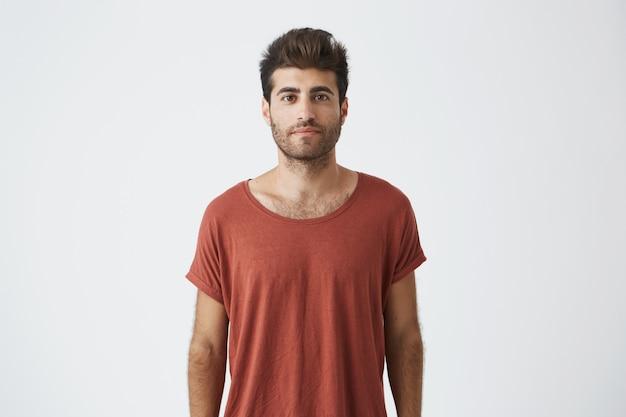 茶色の目で見ているカジュアルな赤いtシャツを着ているトレンディなヘアカットのスタイリッシュなひげを生やした男の肖像。見て満足している若いハンサムな男。人と感情の概念