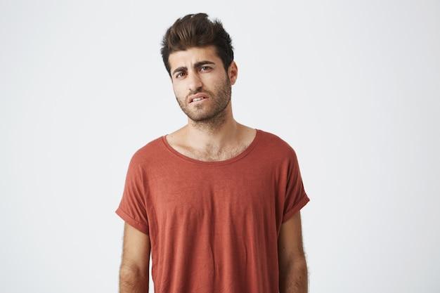 赤いtシャツを着た若い日焼けした学生は、彼の仕事を中断する新しい大学の授業スケジュールに腹を立てています。勉強のつらい時。
