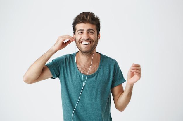 手でヘッドフォンを押し、音楽を聴くと幸せな表情で踊る青いtシャツで陽気なヒスパニック系の男の肖像。前向きな感情とユーモア。
