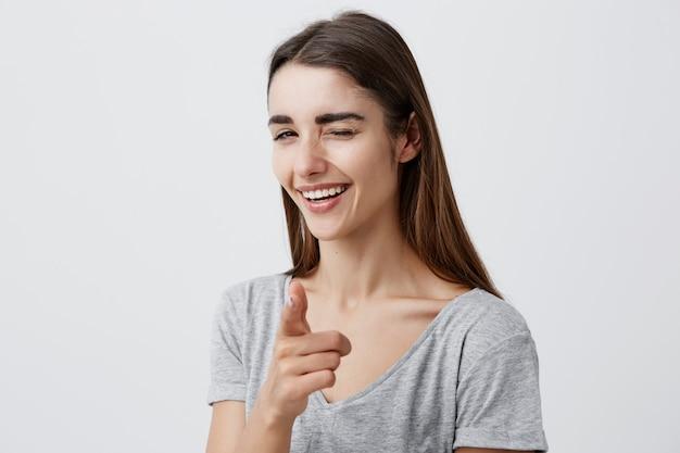 スタイリッシュなプレーンtシャツの長い髪の美しいセクシーな暗い髪の白人少女は、歯で笑顔、まばたき、指で指し、幸せと満足の表情でポーズします。