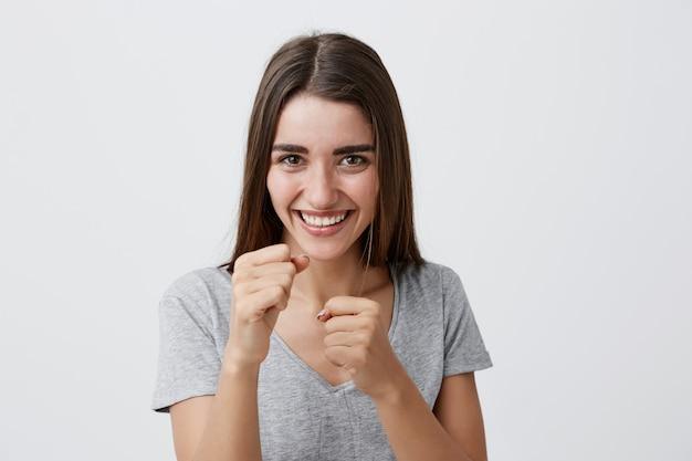 ポジティブな感情。カジュアルなプレーンtシャツの長い茶色の髪と笑って、陽気な表情の戦いのポーズで彼女の前で手を繋いでいる幸せな若いハンサムなうれしそうな女の子。