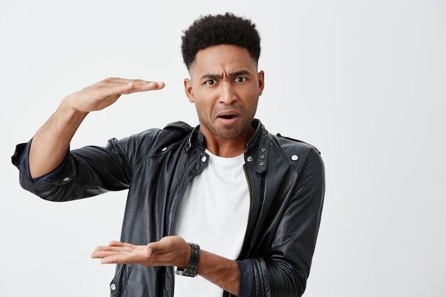 白いカジュアルなtシャツに巻き毛の不幸な成熟した黒肌アフリカ男子学生のクローズアップと怒っている表情でカメラを見ている手で大きなサイズを示す黒い革のジャケット。