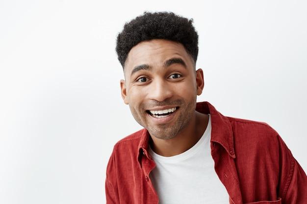 スペースをコピーします。カジュアルな白いtシャツでアフロの髪型と興奮した表情でカメラで見ている赤いシャツの若い魅力的な黒肌陽気な幸せな男の肖像画を間近します。