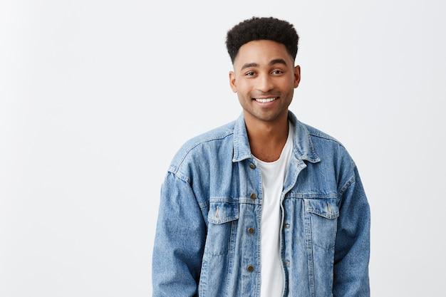 白いtシャツでアフロの髪型とカメラで明るく笑みを浮かべてデニムジャケットの若い美しい陽気な浅黒い男性大学生の白い肖像画に分離されたクローズアップ。コピースペース