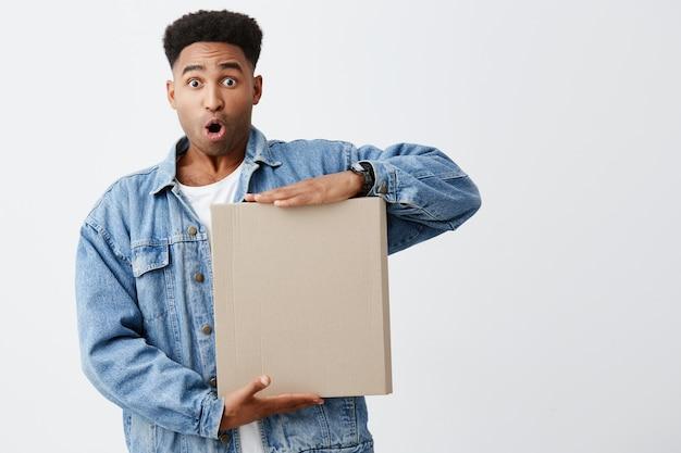 それは何ですか。白いtシャツでアフロの髪型と驚きと好奇心が強い表現で手でボックスを保持しているデニムジャケットで美しい浅黒い肌の面白い男性学生の白い肖像画に分離