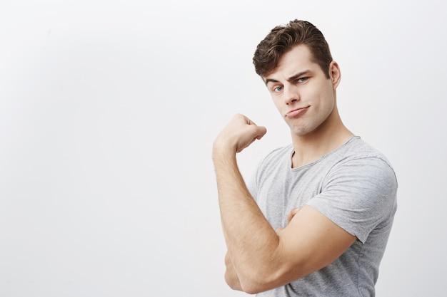 若い肯定的な筋肉男は灰色のtシャツを着て、ジムでトレーニングした後、上腕二頭筋を示し、彼がどれほど強いかを示しています。あざける、顔を男性にして彼の強さを誇りに思う、彼の強い腕を示す