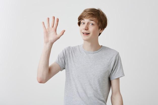 灰色のtシャツに身を包んだ笑顔のこんにちはと挨拶し、手を振って優しそうな丁寧な若い白人男性。肯定的な人間の感情、顔の表情、感情、態度、反応