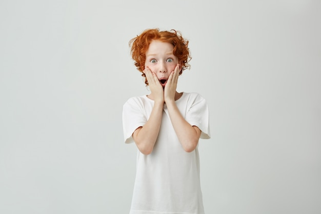 興奮して白いtシャツでそばかすのあるかわいい赤毛の男の子の肖像画