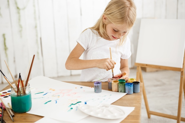 焦点を合わせてインスピレーションを得た小さなブロンドの女の子がブラシをペイントに深く混ぜ、それを混ぜます。絵画で占められた白いtシャツの女性のそばかすのある子供。
