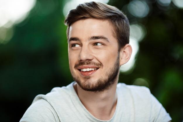 ぼやけて屋外の自然に目をそむける白いtシャツでハンサムな笑みを浮かべて若い男の肖像画を間近します。