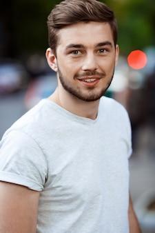 ぼやけた屋外の自然に白いtシャツでハンサムな笑みを浮かべて若い男の肖像画を間近します。