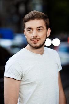 ぼやけた屋外の自然に目をそむける白いtシャツでハンサムな自信を持って若い男の肖像画を間近します。