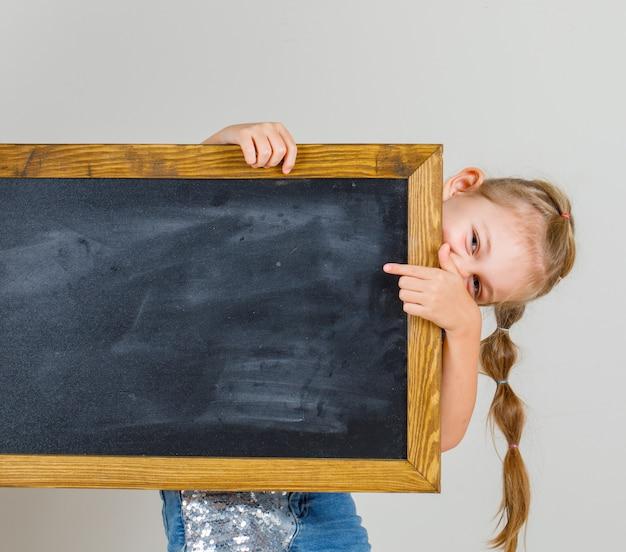 Tシャツとデニムのスカートで黒板を指して、幸せそうに見えて、正面の少女。