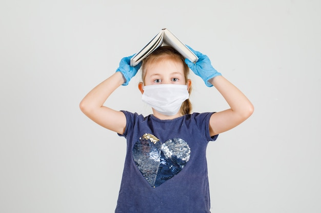 Tシャツ、手袋、マスクの正面で彼女の頭に本を置く少女。