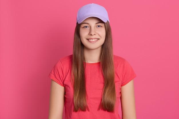 バラ色の壁の上に孤立した立っているカジュアルなtシャツを着ている若い女性に合います。野球帽の美しいモデル