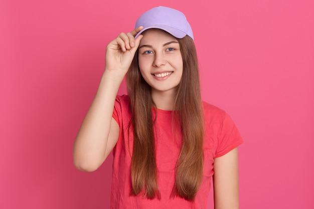 赤いカジュアルなtシャツと野球帽を身に着けている、気分が良く、キャップバイザーに指を置いたまま笑顔の望ましい若い学生の女の子