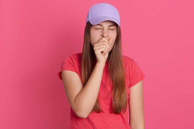 Tシャツと野球帽を身に着けている疲れたあくびの女性のポートレート、クローズアップ、拳で口を覆っている