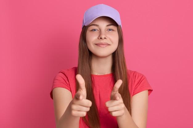 満足そうな表情で指している陽気な素敵な女性は、ピンクの壁に孤立したポーズの赤いtシャツと野球帽を身に着けている満足そうな表情をしています。