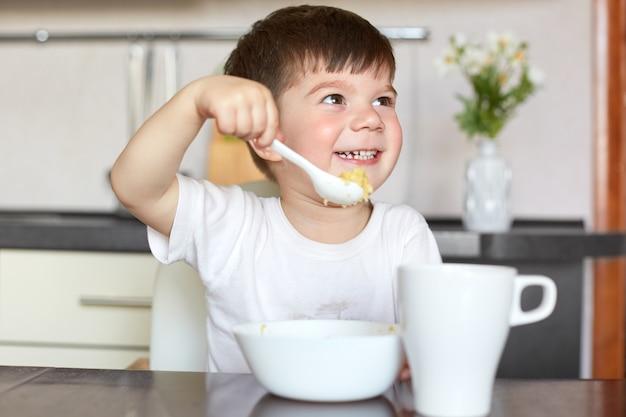 カジュアルなtシャツで幸せな男性の子供はおいしいお粥を食べる