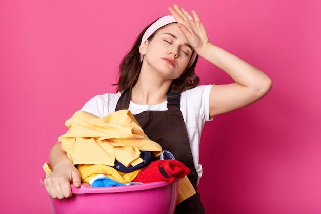 動揺して疲れた表情の居心地の良い主婦は、茶色のエプロンとカジュアルな白いtシャツを着て、ピンクの壁にポーズをとって、自宅でのハードワークの後に疲れきっています。コピースペース。