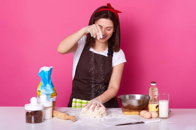 生地の上に小麦粉をまぶし、自家製ペストリーを調理し、イースターケーキを焼く、茶色のエプロンを着ている女性、白いtシャツ、赤いヘアバンド。料理、休日の概念の準備。