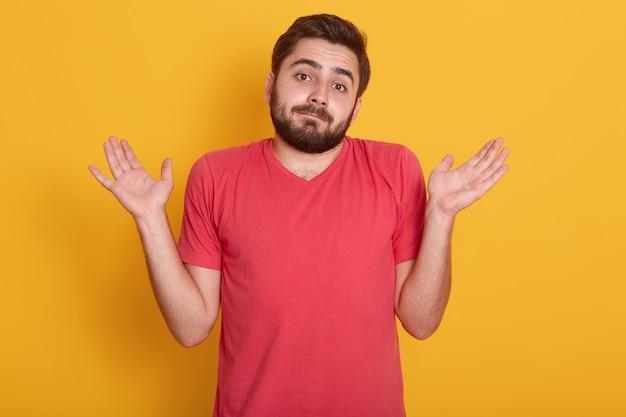 黄色で分離された赤いカジュアルなtシャツのポーズで驚かれる若い男の肖像画を間近します。