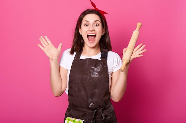ベイカーの若い女性はめん棒を持って両手を上げ、茶色のエプロンと白いtシャツを着て、口を大きく開きます。愛らしいかわいい女性は新しい料理を調理している間元気です。コンセプトを調理します。