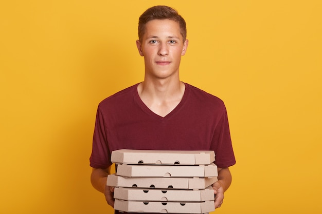ピザの箱を届けるあずき色のカジュアルなtシャツを着ている少年、黄色に分離されたポーズ、カメラ目線、配達人として働いて、彼の仕事をしている深刻な若い女性に見えます。人のコンセプト