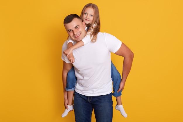 幸せな父と少女が白いtシャツとジーンズを引き裂いて、黄色に分離されたポーズで、一緒に時間を過ごして幸せな表情を持っています。家族の概念。