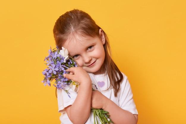 明るい黄色に分離された立っている白いカジュアルなtシャツを着て恥ずかしがり屋で美しい笑顔の女の子は、休日で母親を祝福したいと考えています。母の日おめでとう!子供のコンセプトです。