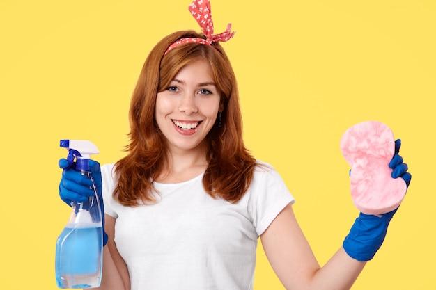 陽気な若い女性の家政婦はカジュアルなtシャツとヘッドバンドを着て、ほこりをきれいに行く、洗浄スプレーとスポンジを保持しています。