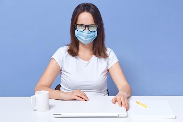 ホーン、カジュアルな白いtシャツ、眼鏡、医療マスクを身に着けている女性で働いているフリーランサーの会計士の屋内撮影