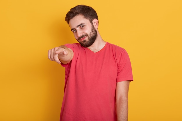 カメラを指して、ながら笑みを浮かべて、赤いカジュアルなtシャツを着て幸せな若い男の肖像画を間近します。
