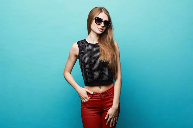 黒いtシャツ、赤いズボン、トレンディなサングラスブルー、分離でスリムなボディを持つ若いモデルの女性