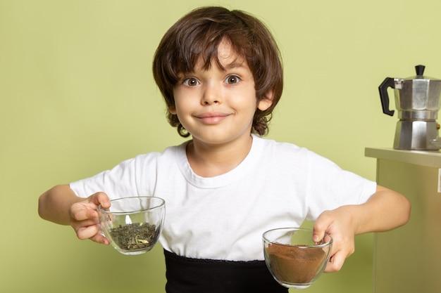 石色のスペースでコーヒーを準備する白いtシャツで正面笑顔少年