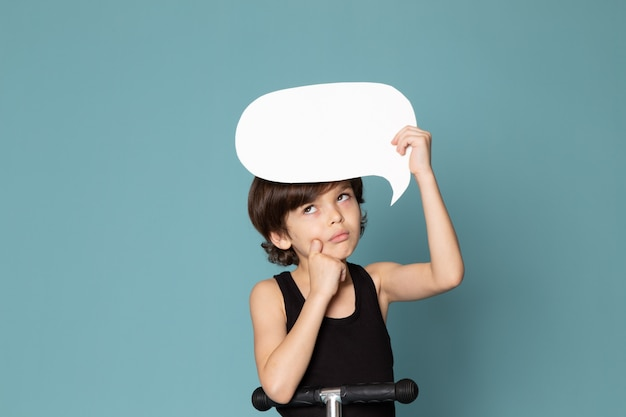 青いスペースに黒いtシャツに白い看板を持っている正面思考子供男の子