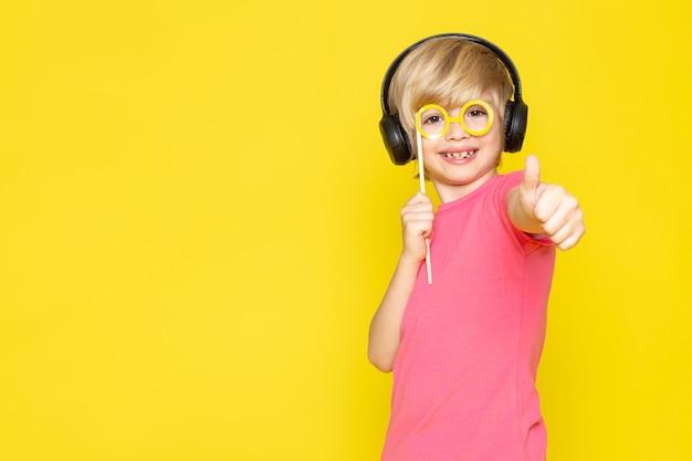 ピンクのtシャツと音楽を聴く黒いヘッドフォンの少年