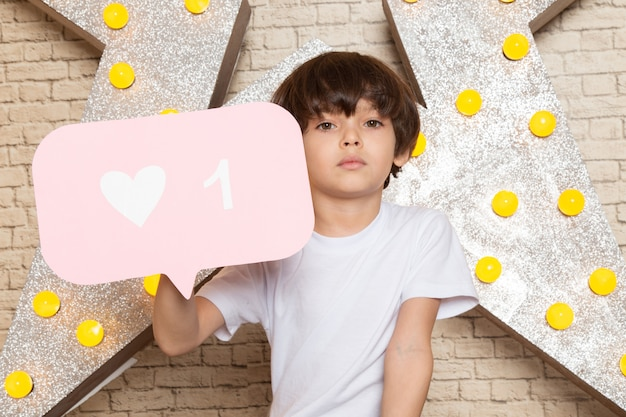 星に白いtシャツダークジーンズで正面のかわいい子供は黄色のスタンドと明るい背景を設計