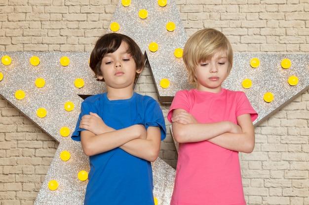 星の青いとピンクのtシャツダークとグレーのジーンズで正面のかわいい子供たちは黄色のスタンドと明るい背景を設計