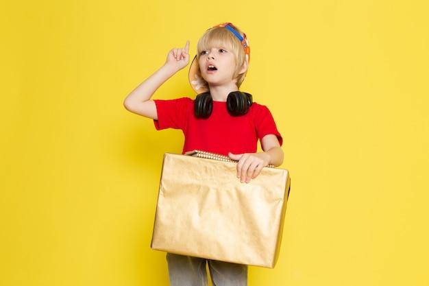 赤いtシャツのカラフルなキャップと灰色のジーンズの黄色の背景にボックスを保持している小さな男の子の正面図