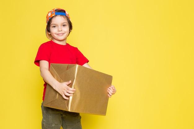 赤いtシャツのカラフルなキャップと黄色の背景にボックスを保持しているカーキ色のズボンの正面の小さな男の子